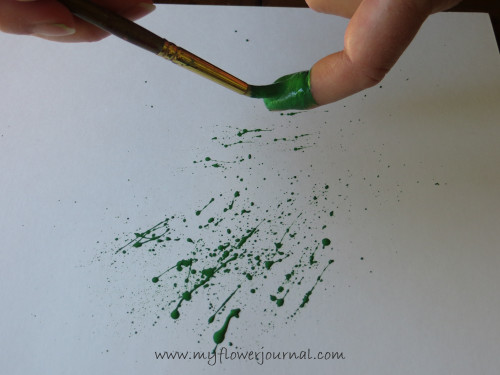 Load your brush with paint and flick it across your index finger to create the splatters for your splattered paint art-myflowerjournal.com